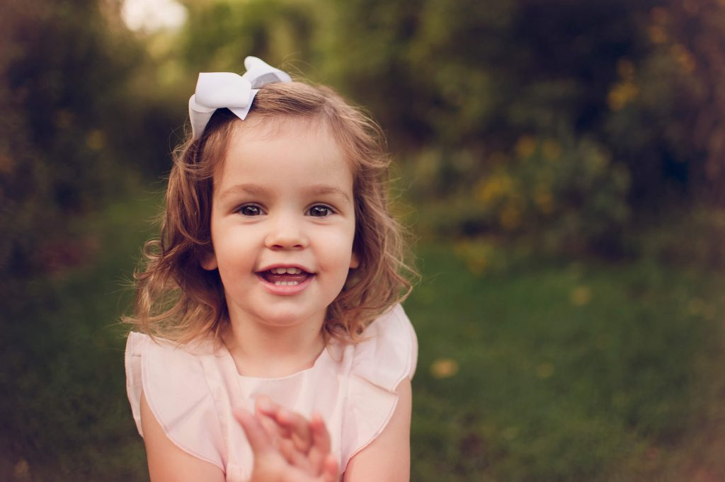 Little girl wearing pink dress and bow in her hair laughing at Canton home photo session.