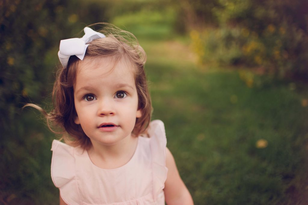 Little girl wearing pink dress looking off camera in family photo session in Canton, OH.
