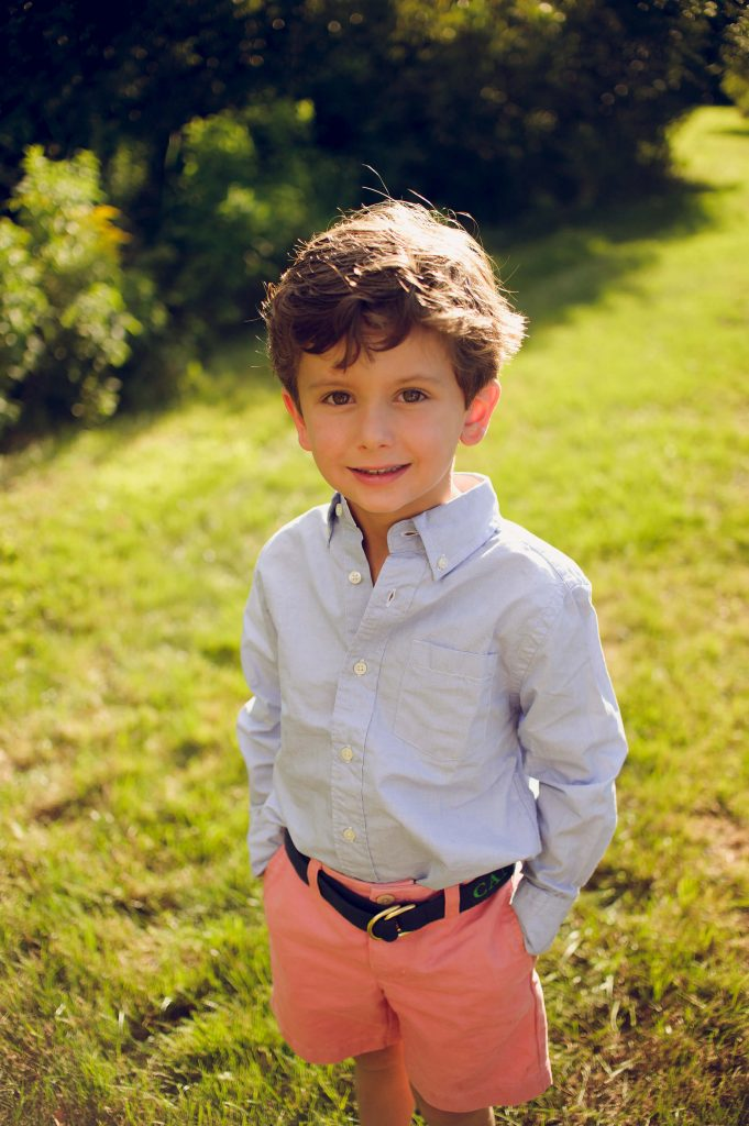 Boy wearing collared shirt and shorts with hands in pockets smiling for photo.