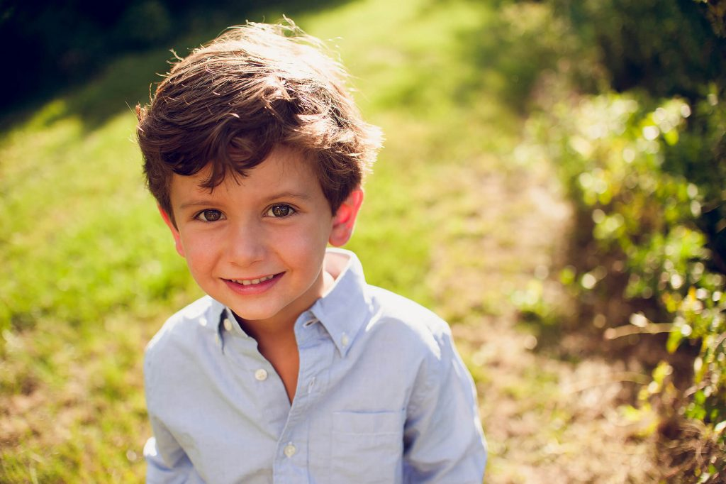 Portrait of young boy in blue shirt smiling at sunset family photo session.