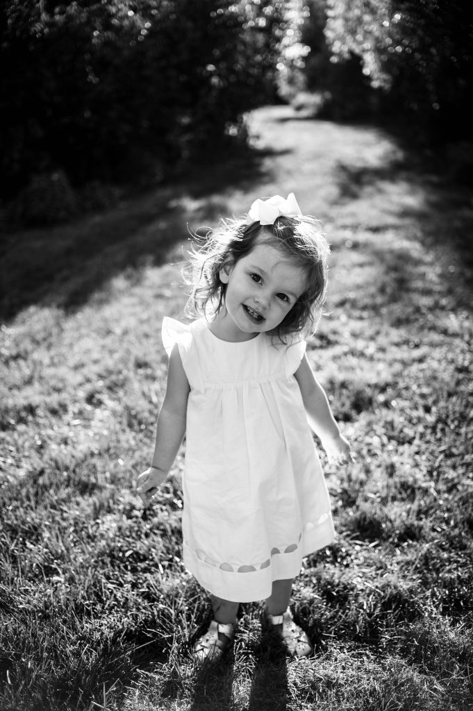 Black and white image of little girl in sunset light at Canton, OH home.