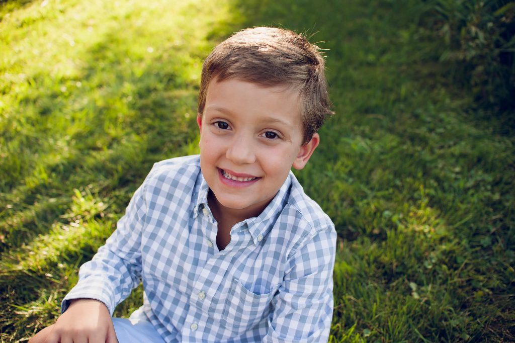 Little boy sitting in the grass smiling for photo.