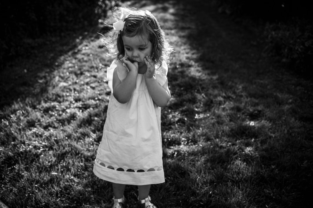 Little girl wearing dress and sucking thumb outside at photo session in Canton.