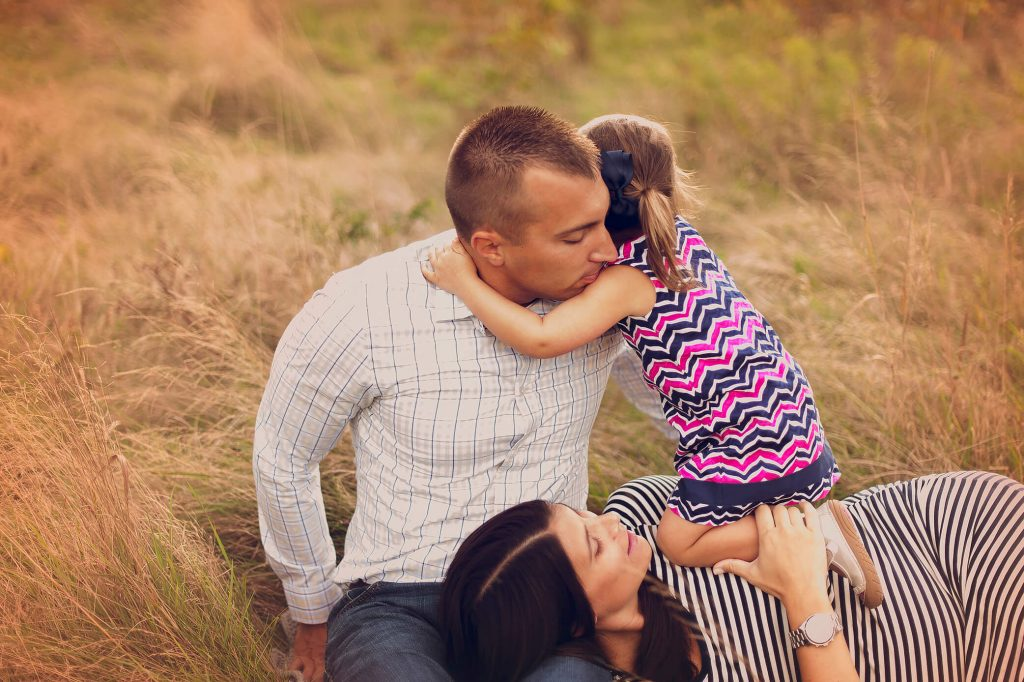 Girl hugging dad around neck while mom lays on his lap in family photo session near Cleveland, OH