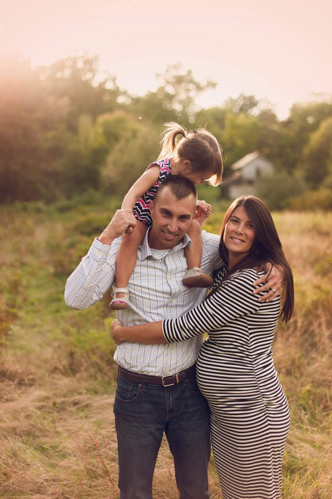 Pregnant mother hugging husband with child on his shoulders during family photo session.