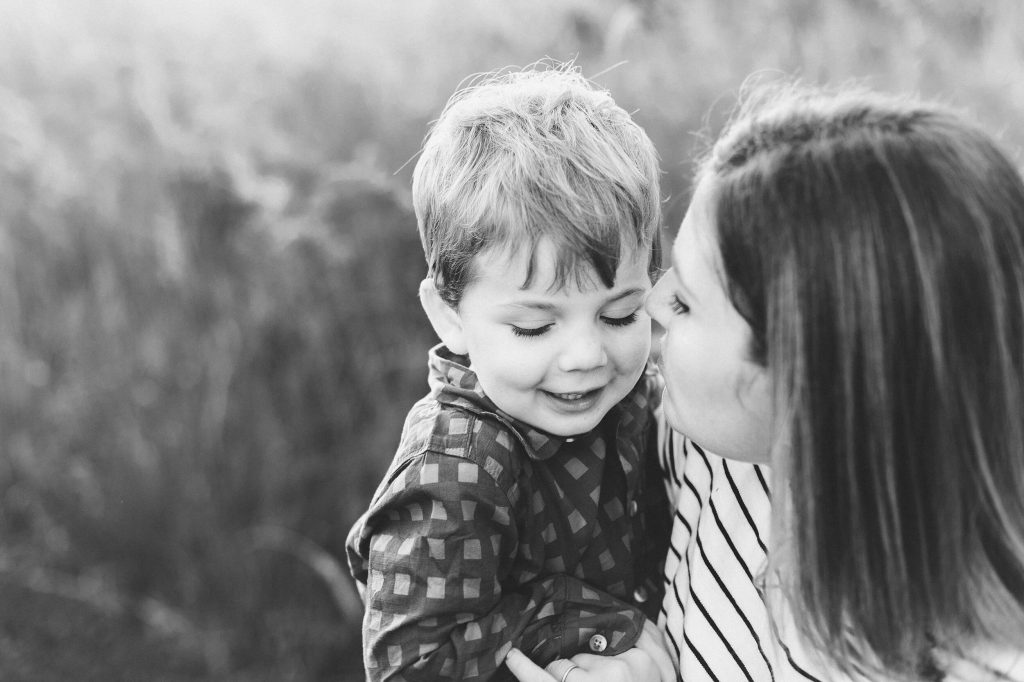 Black and white image of son with mom giving kiss on his cheek at Wolf Creek Lodge field.