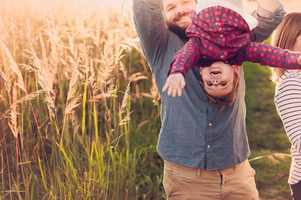 Dad holding son upside down in Medina field at sunset family photo session.