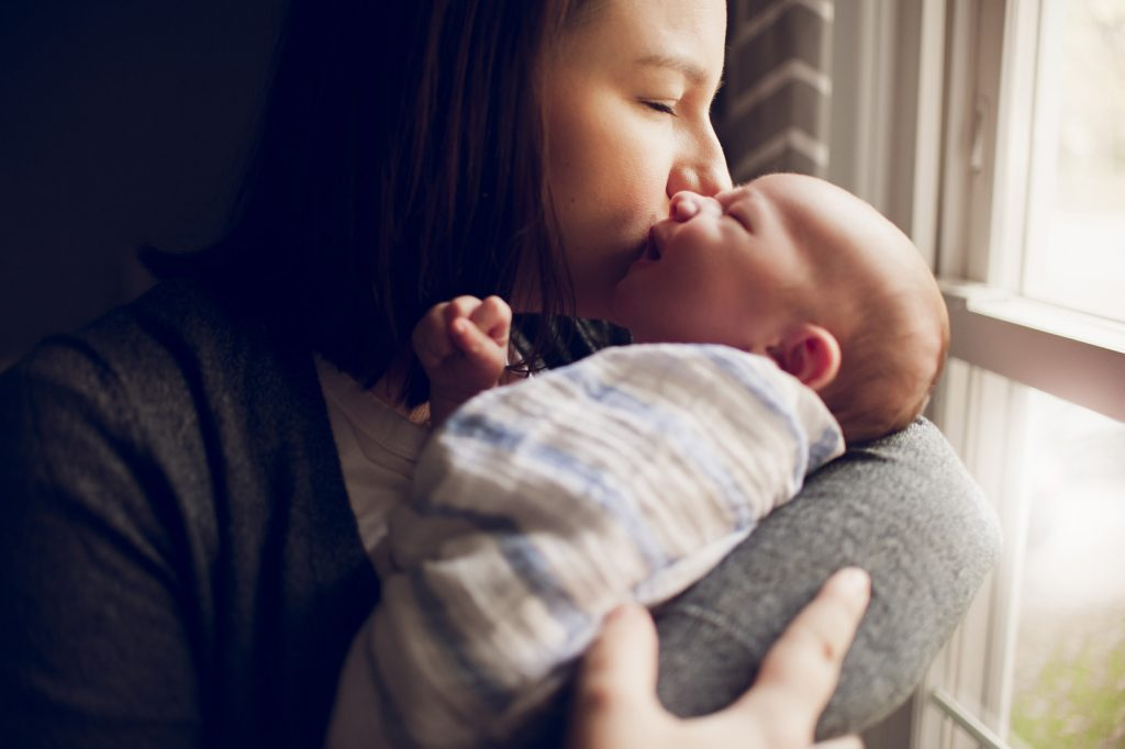 Mother kissing newborn son in Cleveland home nursery.