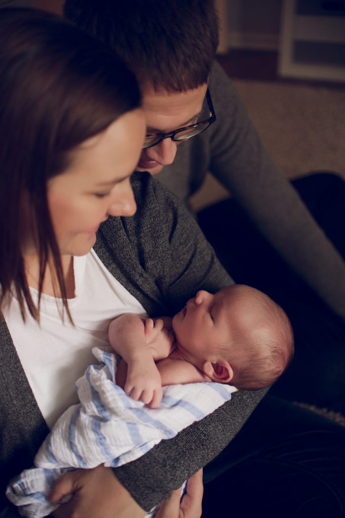 Parents holding newborn boy looking at him during newborn session in Cleveland home.