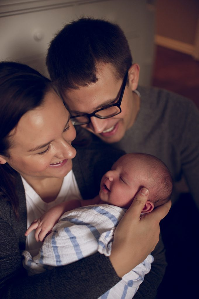 Parents smiling at smirking baby boy during newborn session.