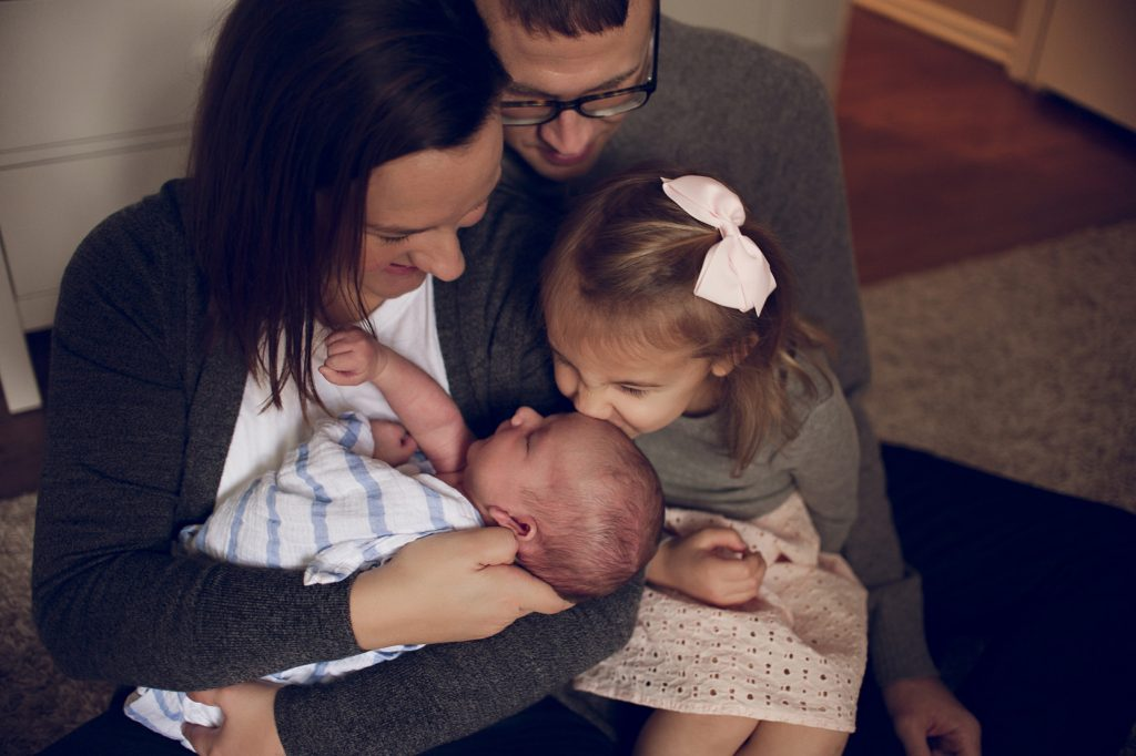 Family of four in newborn nursery in Cleveland home.