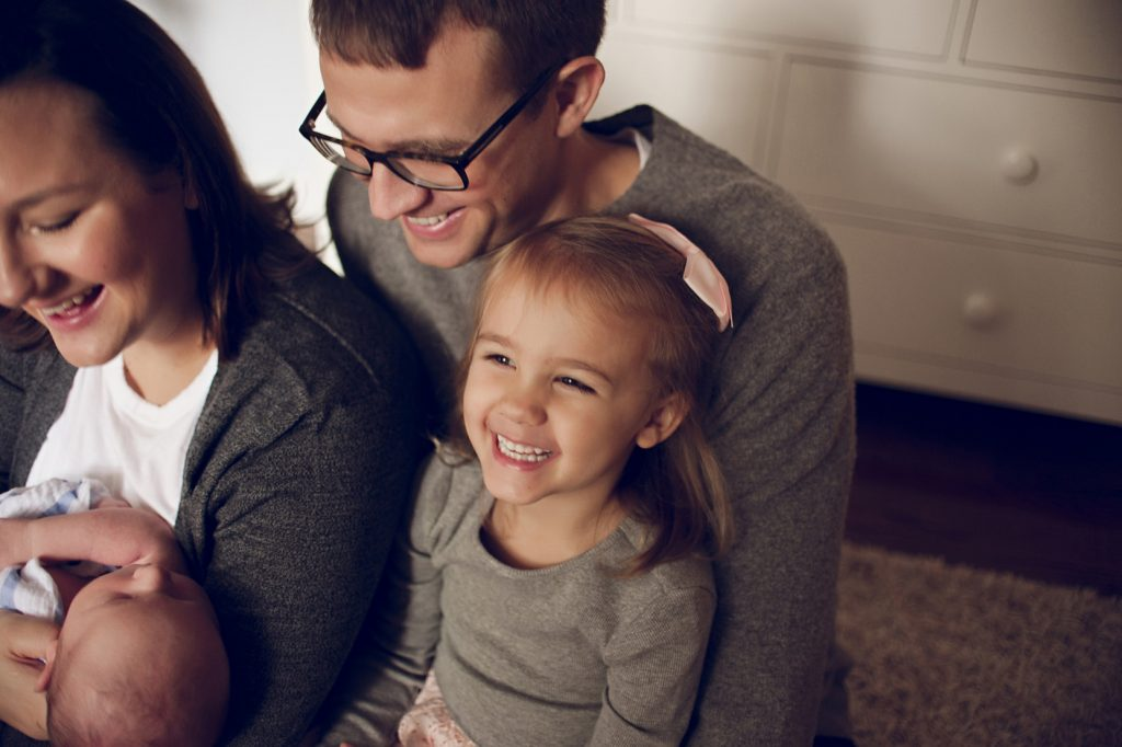 Little blonde girl sitting on dad's lap laughing during newborn photo session in Cleveland home.