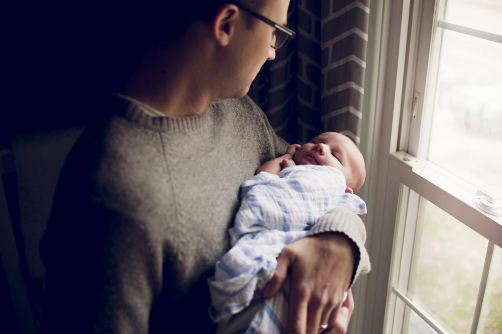 Dad holding new baby son near nursery window.