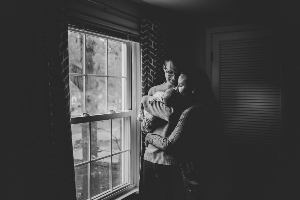 Black and white image of parents holding baby boy.