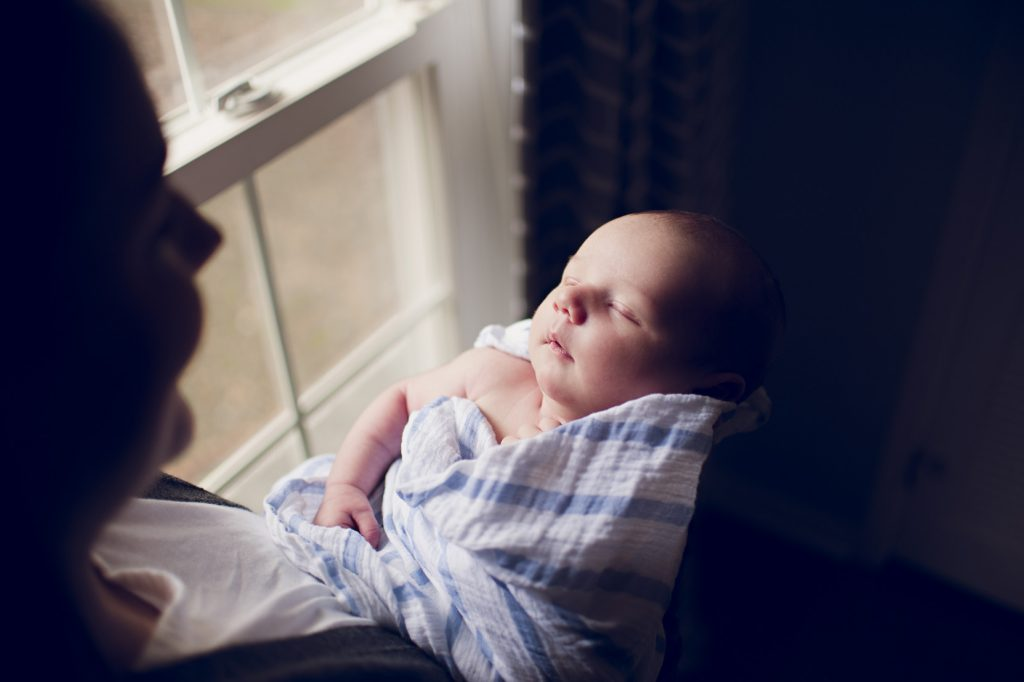 Mom holding baby boy in striped blanket by nursery window.