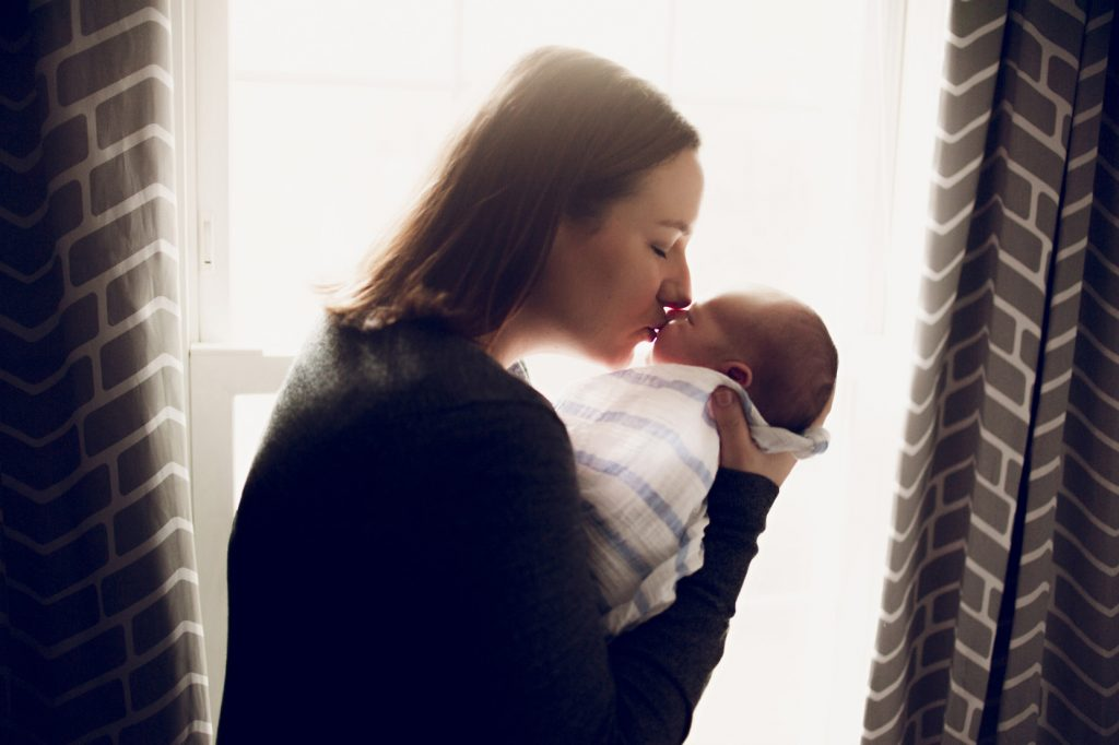 Mother kissing baby boy in front of home window in Cleveland.
