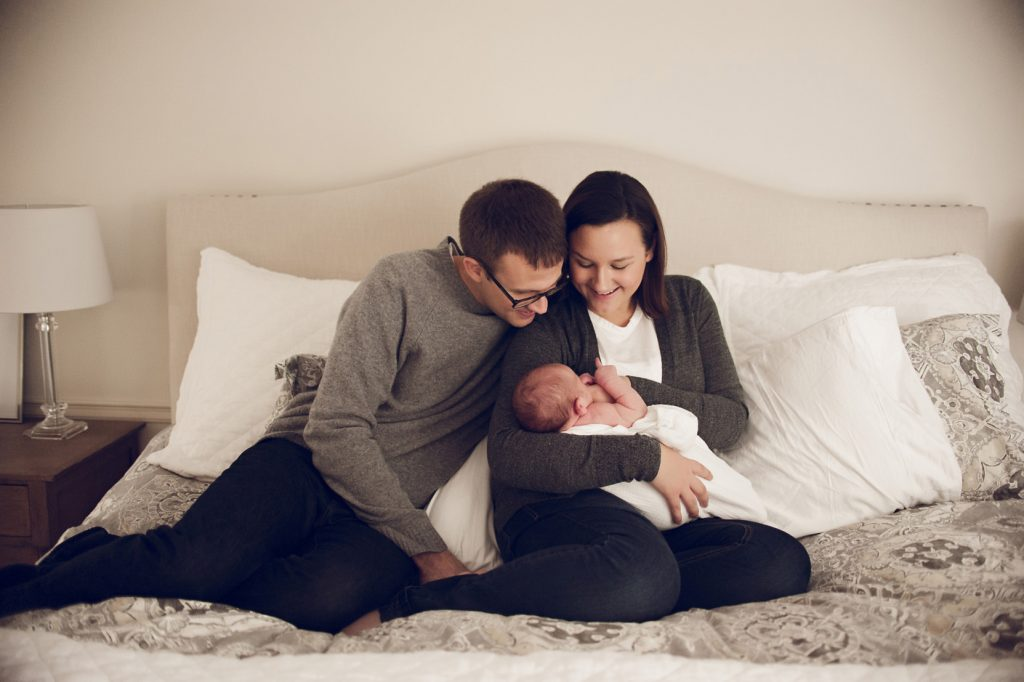 Couple holding baby on their bed in Cleveland home during newborn photo session.