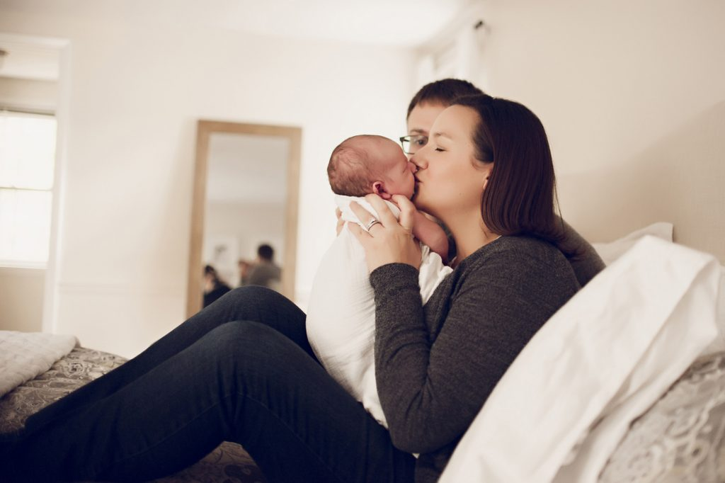 In-home newborn photo session with mom holding baby up and kissing cheek.