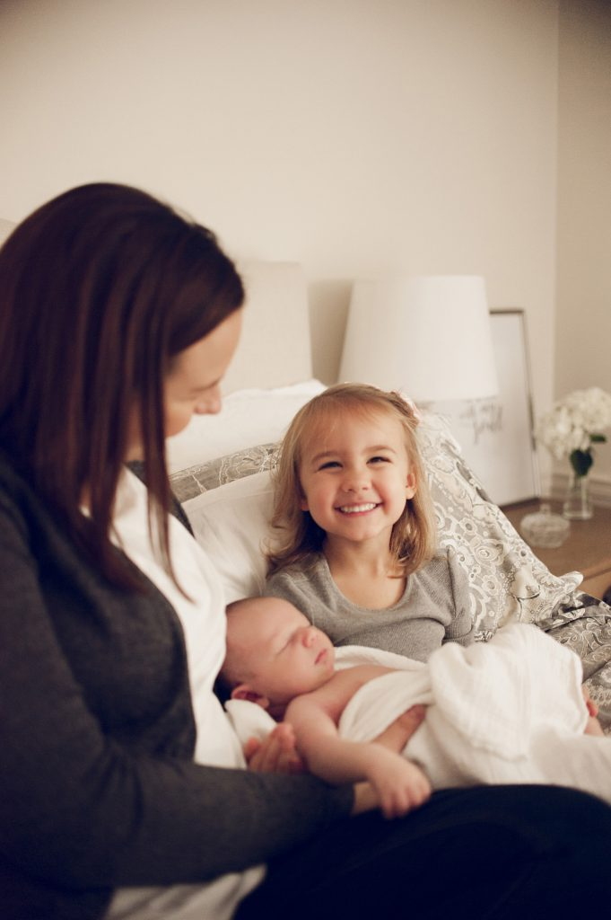 Happy smiling little girl holding baby brother on parent's bed.