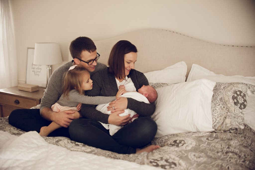 Family sitting on bed in Cleveland home adoring baby boy.
