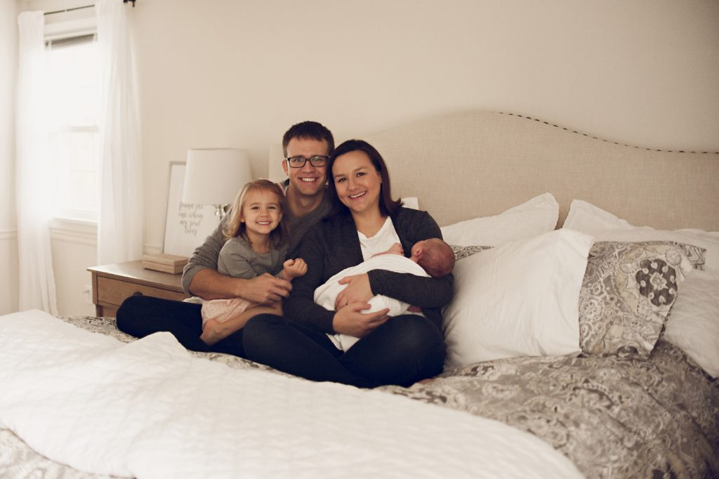 Family smiling for portrait on bed during newborn session in Cleveland home.