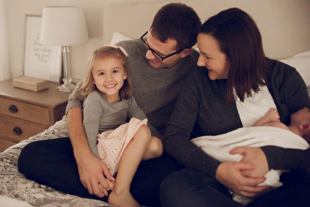 Family with little girl and newborn boy smiling on bed for portrait.