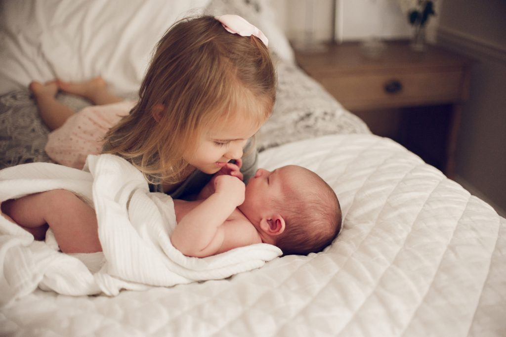 Little blonde girl looking at baby brother during newborn session in Cleveland.