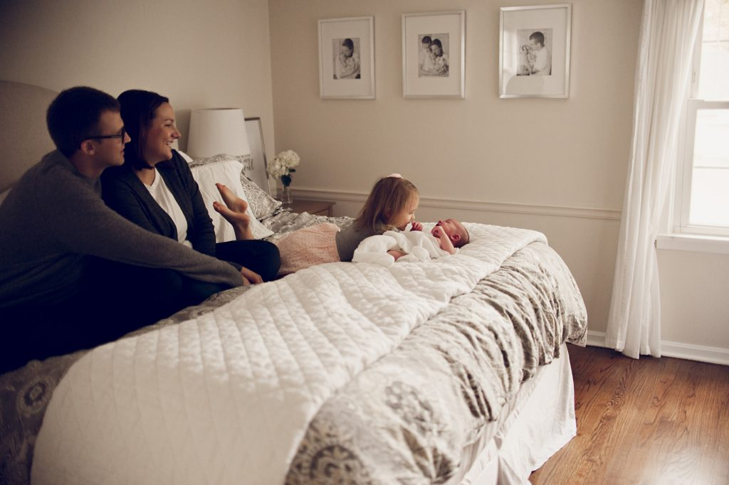 Family playing on bed in Cleveland newborn home session.