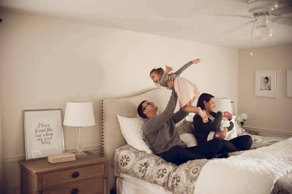 Family playing on bed with dad holding girl in the air and mom holding newborn.