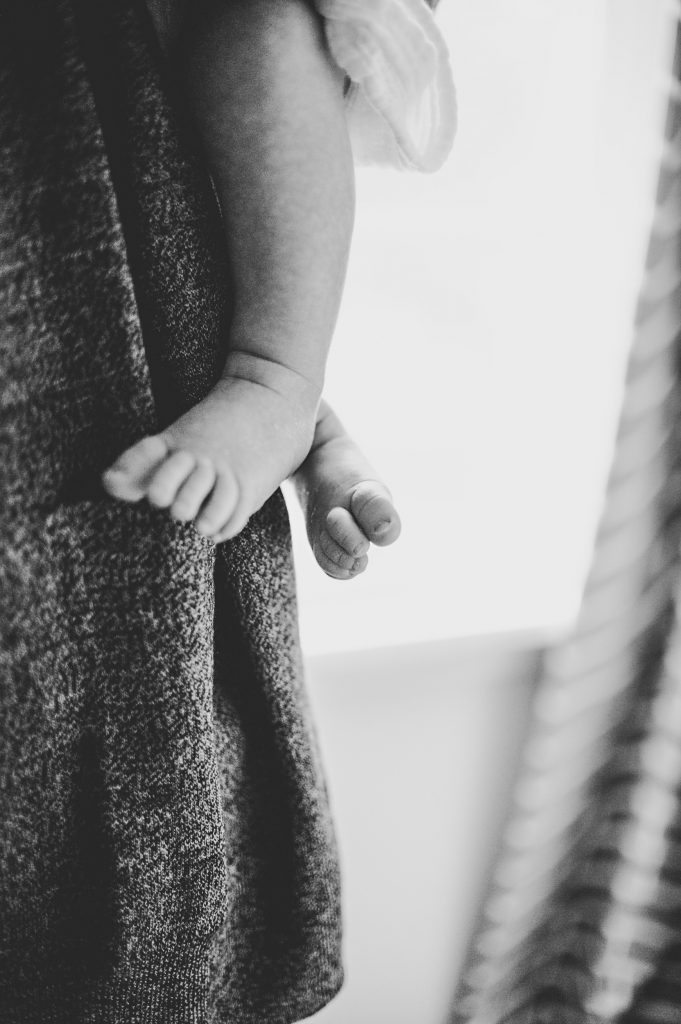 Black and white image of newborn baby feet in nursery.