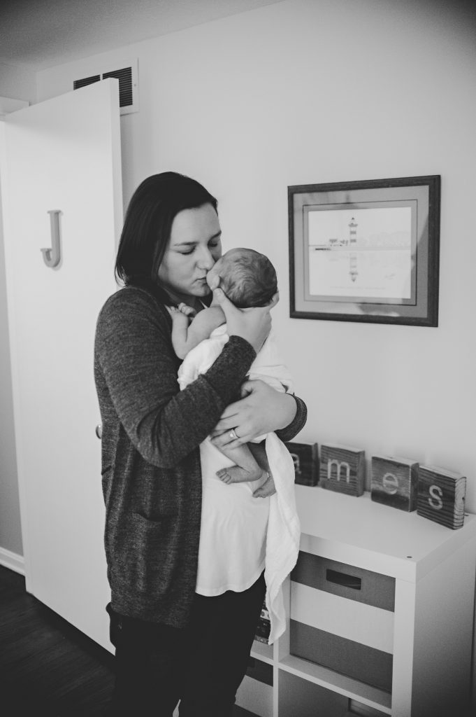 Black and white image of mom standing holding baby boy in nursery.