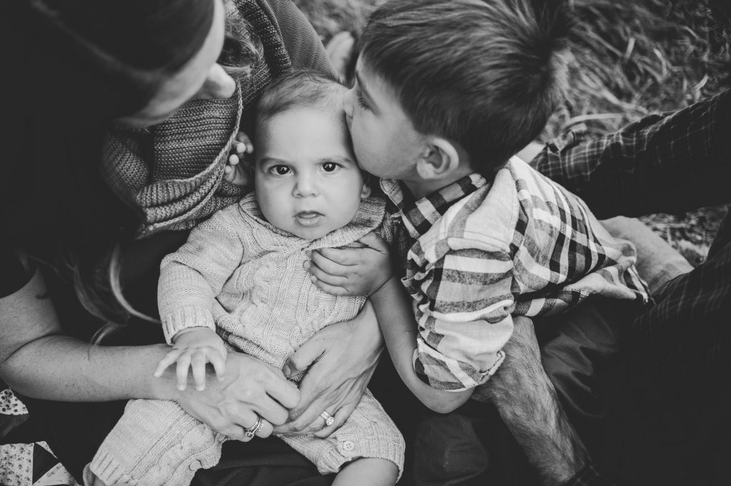 Black and white image of little boy giving baby a kiss during fall apple orchard family photos.