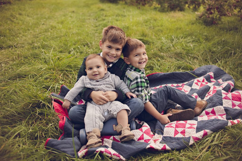 three young boys sitting in apple orchard for photos.