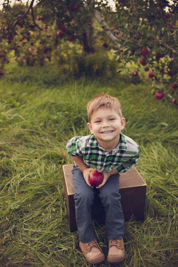 Little boy sitting on wooden box holding apple.