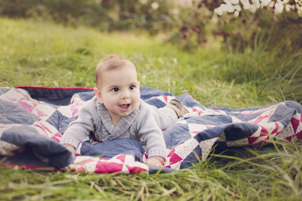 Baby boy in quilt during family portrait session in apple orchard.