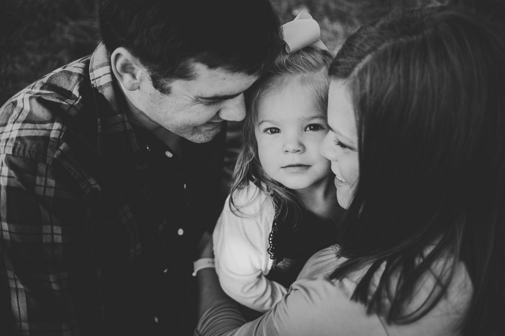 Black and white image of family with little girl.