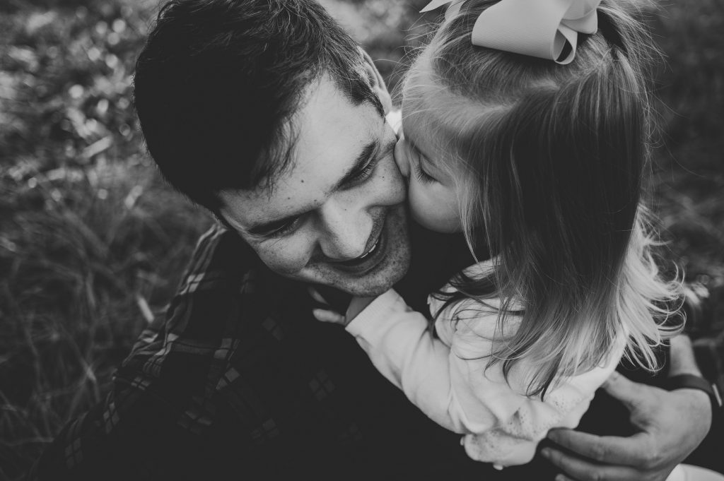Black and white image of little girl giving dad kiss on the cheek during portraits in apple orchard.