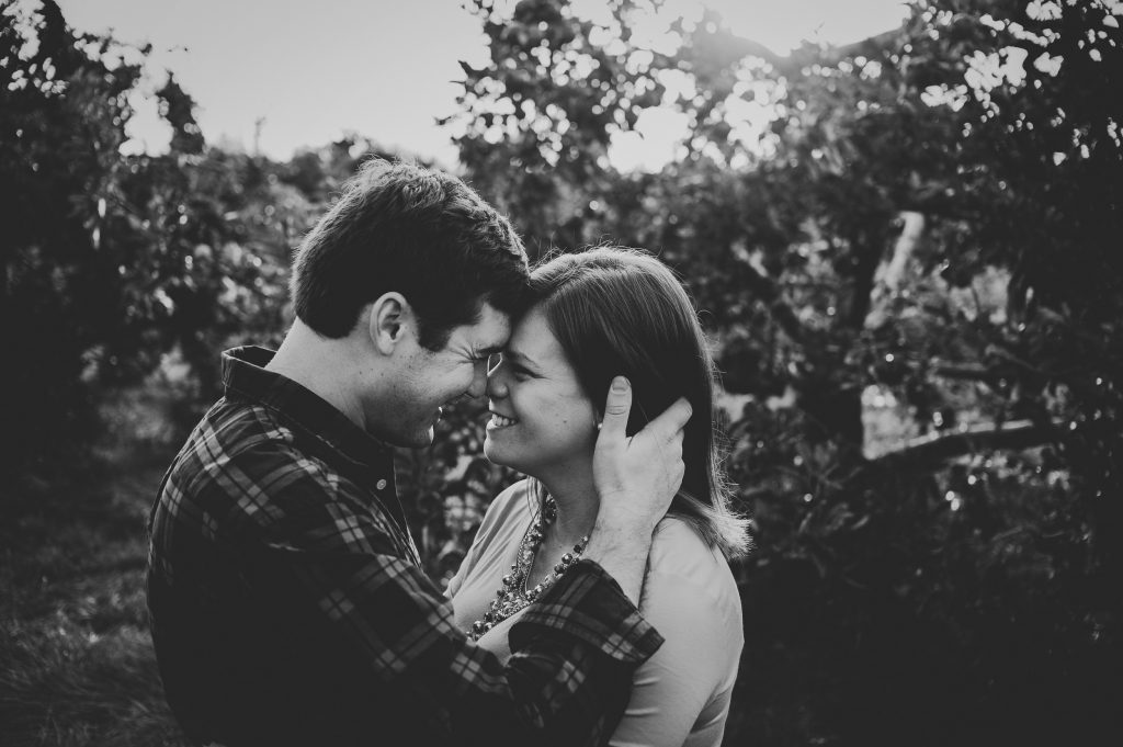 Married couple smiling at each other with heads together in apple orchard.