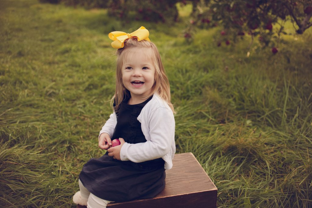 Little girl in dress and yellow hair bow sitting on a box during family apple orchard pictures.