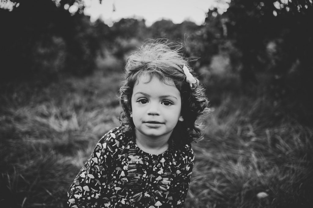 Black and white image of little girl in windy apple orchard.