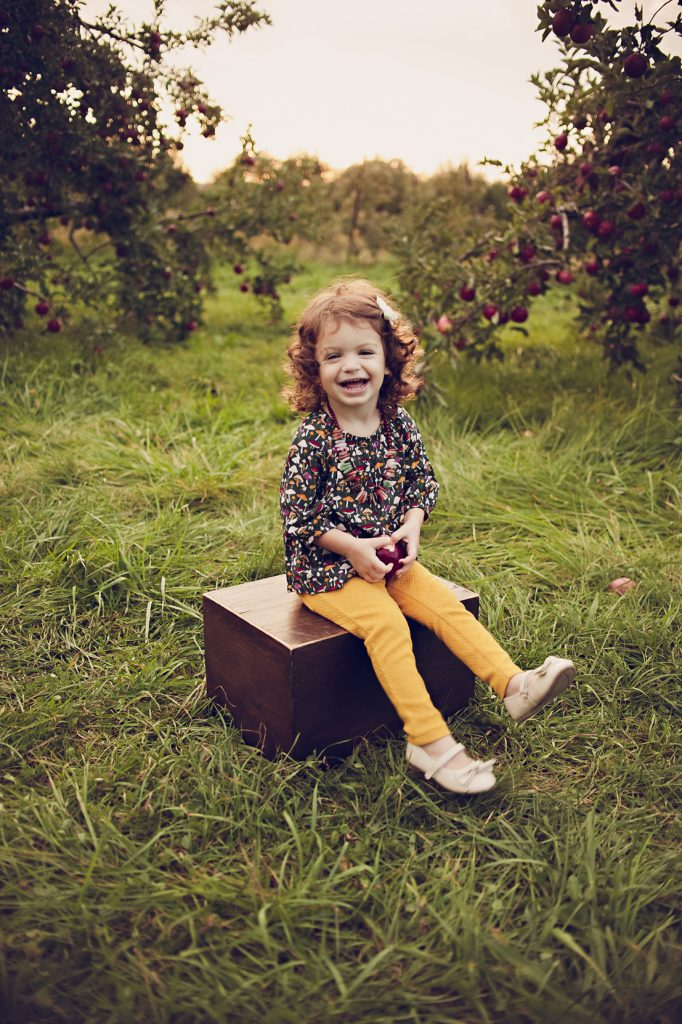 Little girl sitting on wooden box in apple orchard laughing for a picture.