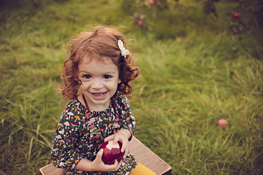 Little girl holding bitten red apple in orchard for portraits near Cleveland.