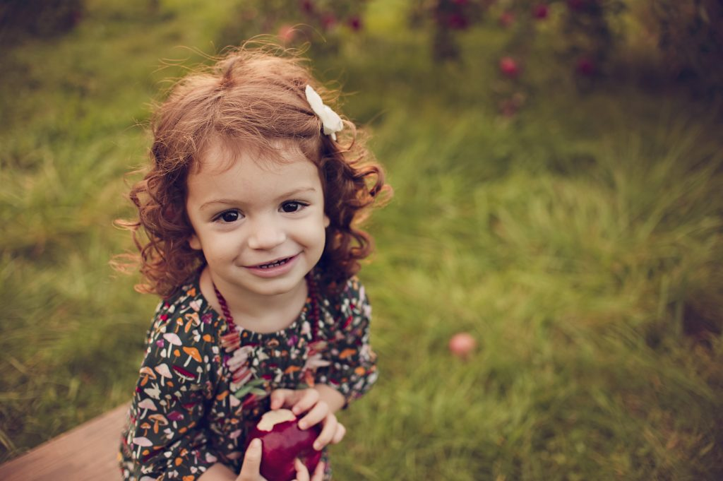 Cute little girl holding apple smiling for portrait.