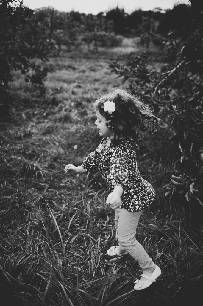 Black and white image of little girl spinning around in apple orchard.