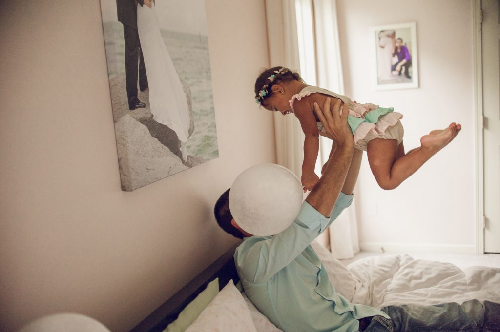 Dad holding daughter above him in bed in Cleveland home.