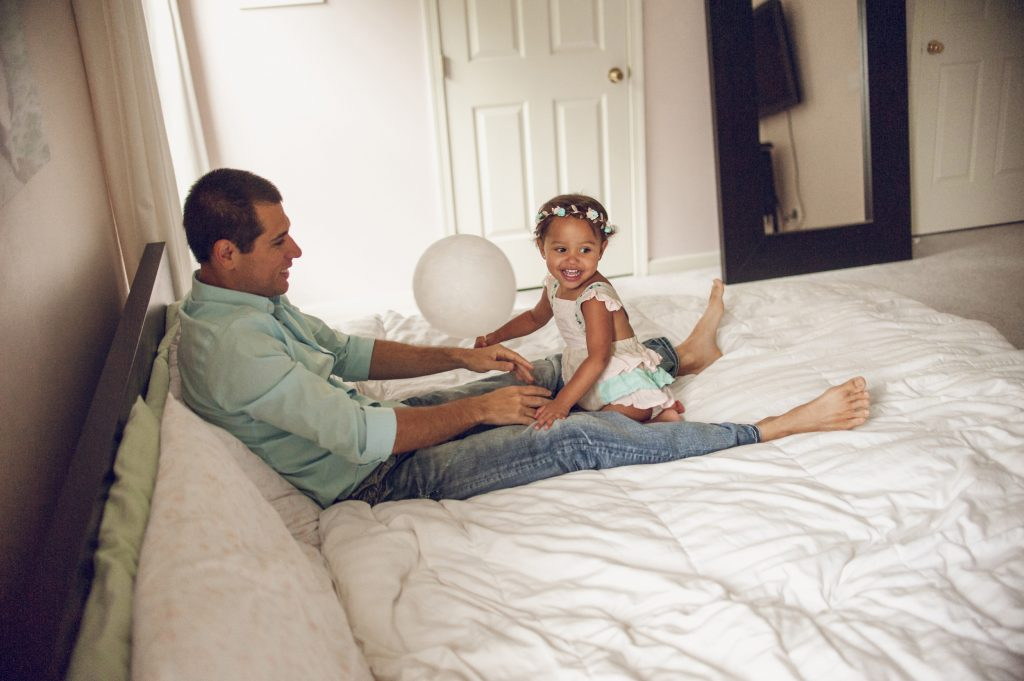 Little girl laughing while playing on bed with dad.