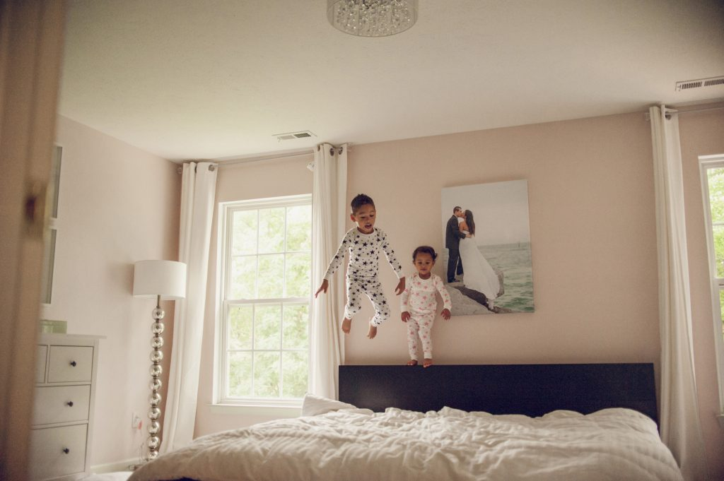 Two little kids jumping on parent's bed.