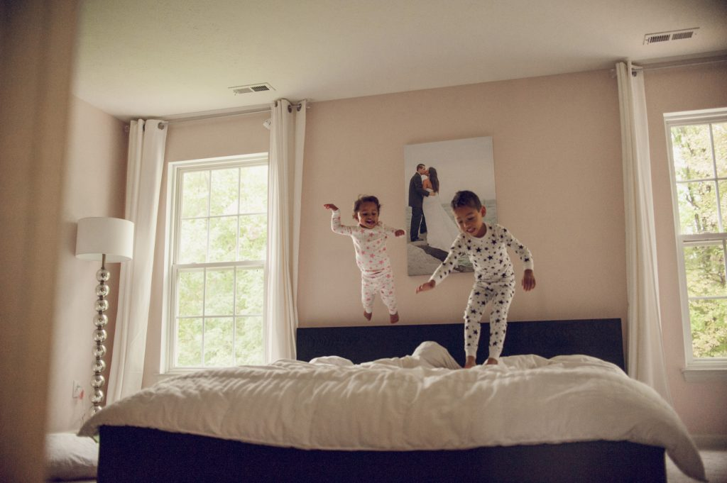 Little boy and girl jumping on parent's bed in Cleveland home.