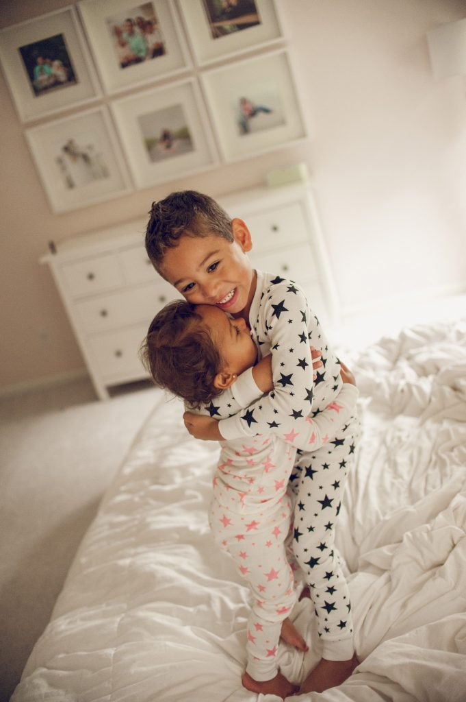 Brother and sister in pajamas hugging and smiling on bed in Cleveland home.