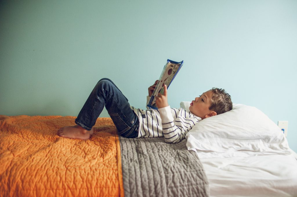 Little boy laying on bed in front of blue wall reading a book.